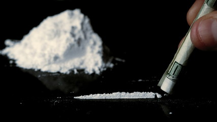 Someone snorting a line of cocaine beside a large pile