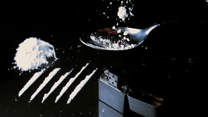 Drugs falling onto spoon beside lines larger pile and lighter