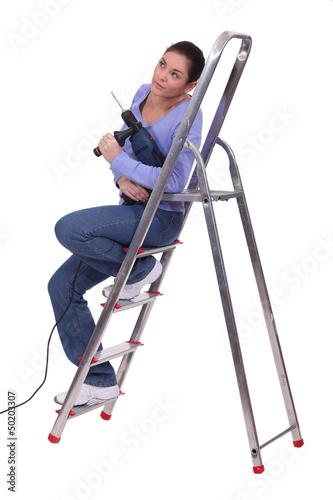 Handywoman sat on a ladder