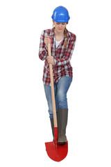 Female laborer digging with shovel