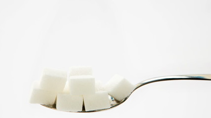 Pile of sugar lumps appearing on teaspoon