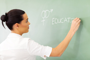 educator writing sex education on chalkboard