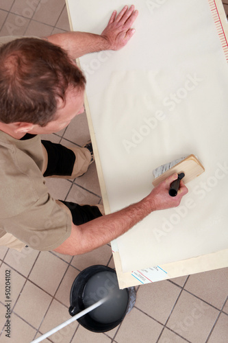 Handyman applying glue on wallpaper