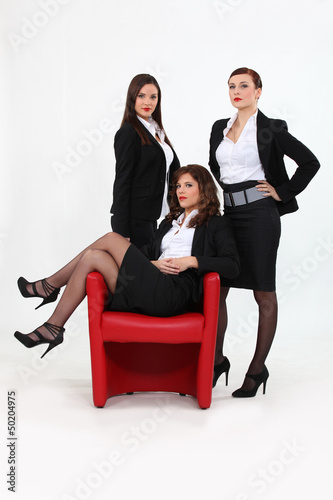 Three confident businesswomen stood by chair