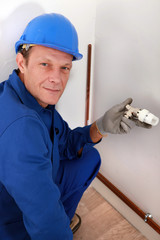 Workman holding a radiator temperature dial