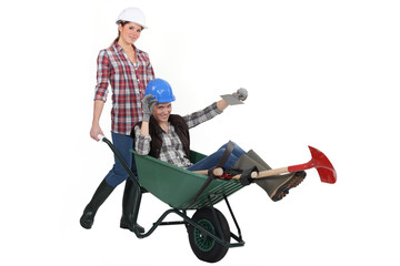 Two women messing around wuth wheelbarrow