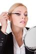 Attractive businesswoman applying mascara