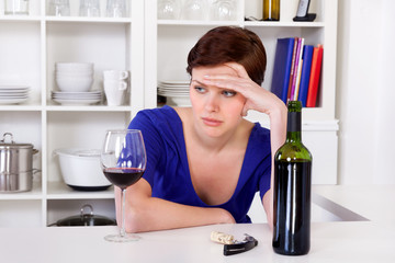 young sad thinkful woman drinking a glass of red wine