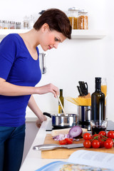 Woman in her kitchen preparing a pasta dish