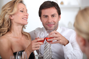 Couple sitting holding wine glasses together