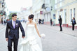 Bride and groom walking together in an old town
