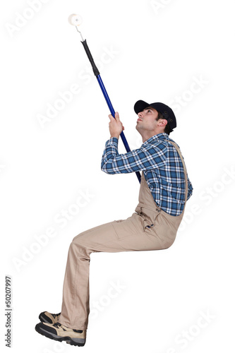 Man painting a ceiling with a roller