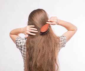 Woman combs her hair