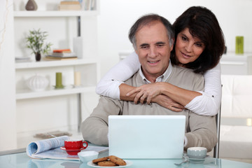 A middle age couple looking at a laptop.