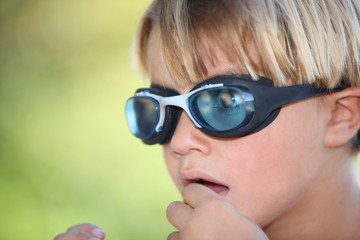 Nervous young boy wearing swimming goggles