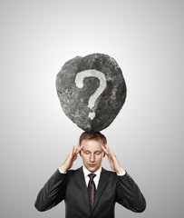 businessman and stone with question on his head