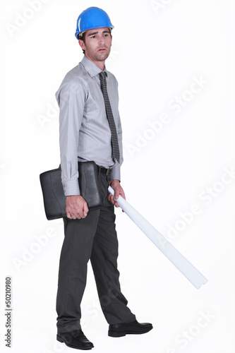 tired businessman wearing helmet and holding a blueprint