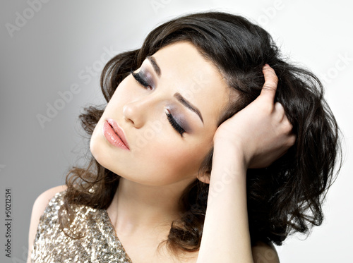 Beautiful woman touches her brown curly hairs