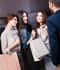 Girls consult with salesperson concerning buying presents