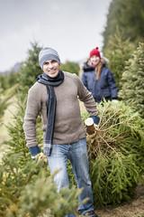 Family with Christmas tree on a farm