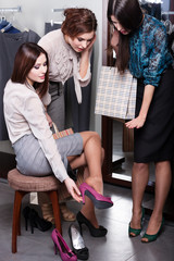 Woman seeks counsel from friends while trying on shoes