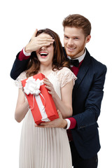 Man closes eyes of his beautiful girlfriend to give a present