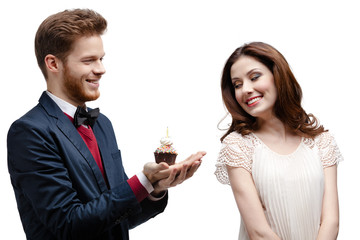 Man presents birthday cake to his girlfriend, isolated on white