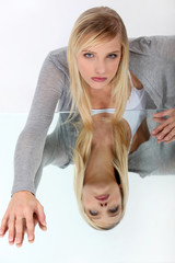 Blond leaning on reflective surface