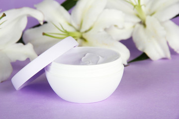 Cosmetic cream and beautiful lily, on purple background