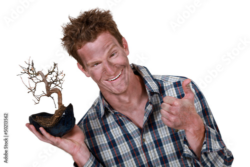 man covered with dust holding a plant root