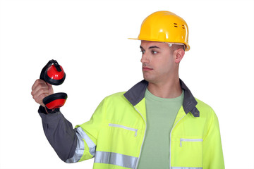 Construction worker staring at his earmuffs