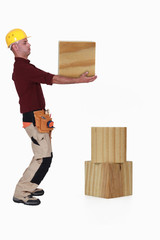 Carpenter lifting heavy block of wood