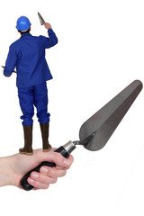 Man with a trowel standing on an arm with a trowel