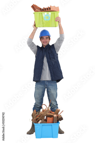 Tradesman posing with recycling bins