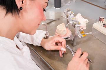 Zahntechnikerin in einem Dentallabor mit Zahnersatz