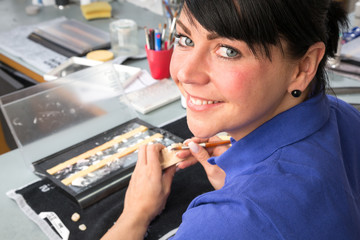 Zahntechnikerin trägt Keramik auf Zahnersatz auf