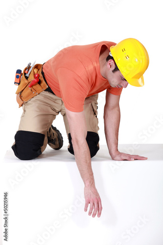 Construction worker reaching down