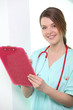 Nurse looking at clipboard smiling