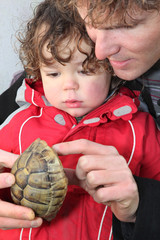 Father and son holding turtle