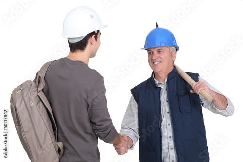 Builder welcoming teenage helper