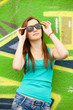 Style teen girl in sunglasses near graffiti background.