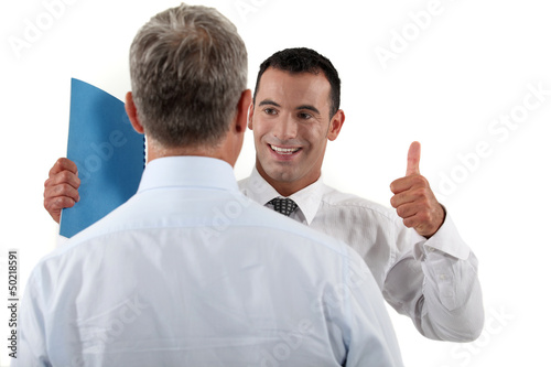 Businessman giving his colleague the thumbs up