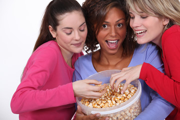 three young women eating popcorn