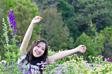 Asian woman relaxing in the garden flowers
