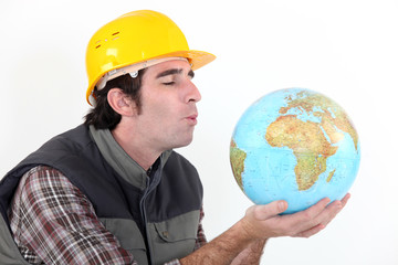 Construction worker blowing on globe