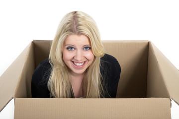 Junge Frau kuckt überrascht lächelnd aus Karton