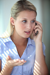 Blond woman having argument over the telephone