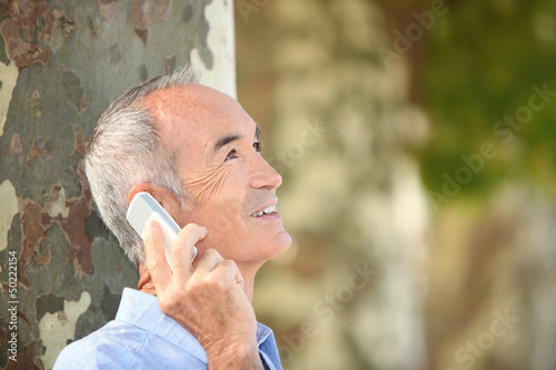 Grey-haired man with mobile telephone stood by tree