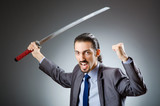 Angry businessman with sword in dark room