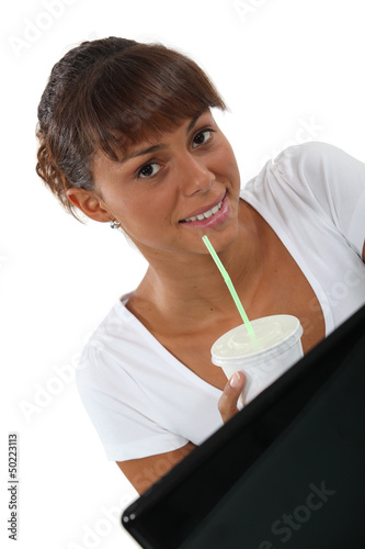 Woman with drink in front of computer
